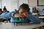 La Academia Mexicana de Ciencias impartió un taller de robótica a 86 menores de la IAP A Favor del Niño. Una niña arma un juguete móvil, que técnicamente es una mesa eléctrica de engranes, partes que integran un robot.