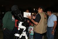 Fidel Torres, de la Sociedad Astronómica Nibiru de la Facultad de Ciencias de la UNAM, explica a una familia lo que a través de la lente del telescopio se puede observar en el cielo.