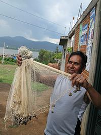 Un pescador del lago de Pátzcuaro muestra una red agallera (nombrada cherémura en tarasco).