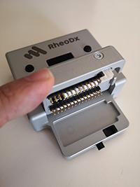 RheoDX o microreoelectrómetro es un aparato que procesa la información de la sangre y controla los canales o chips en los que se deposita el fluido para ser procesado por el instrumento. La ventaja de este dispositivo frente a otros es que en cinco minutos se tiene un diagnóstico.