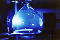Una parte de la preparación experimental del astrobiólogo Rafael Navarro-González, del Instituto de Ciencias Nucleares de la UNAM y co-investigador con el instrumento SAM (Sample Analysis at Mars), y su equipo de científicos para simular los impactos de asteroides en el ambiente marciano primitivo. El matraz (imagen) contiene una composición de dióxido de carbono, nitrógeno y gases de hidrógeno. Un láser infrarrojo de alta intensidad se enfoca en el matraz desde una lente (izquierda) para simular las ondas de choque de alta energía producidas por los asteroides que entran en la atmósfera marciana. Luego, el gas se evacua del matraz y se analiza para determinar la composición y los niveles de fijación de nitrógeno.